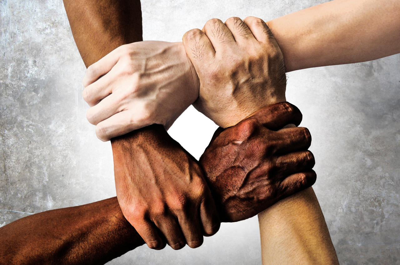 Hands of people from different ethnicities grasp each other
