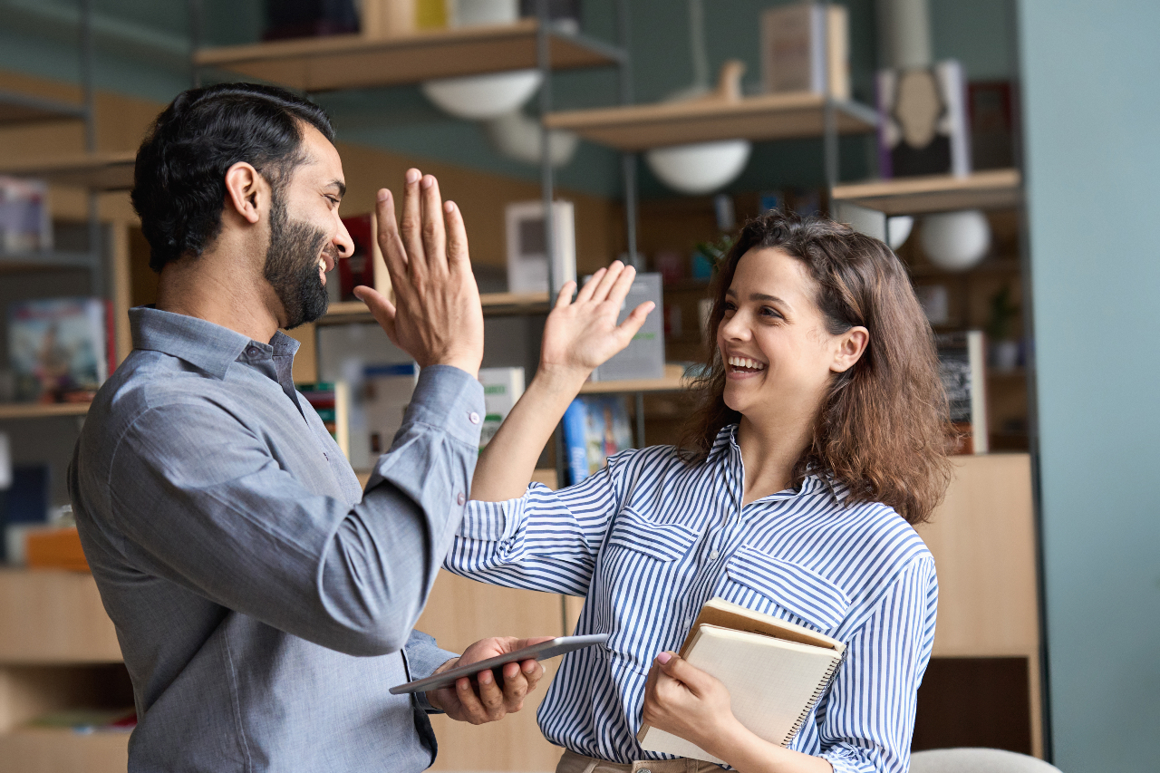 Smiling man and woman holding papers and giving each other a high five