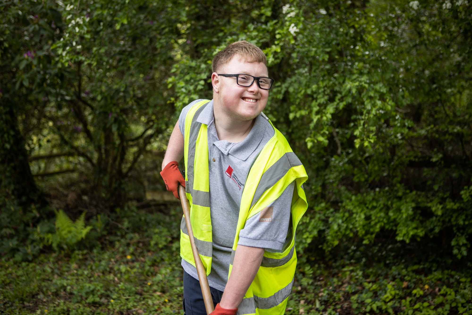 Man in high vis is gardening with Awen Cultural Trust's B-Leaf Centre. B-Leaf is a work based initiative for adults with disabilities based within Bryngarw Country Park
