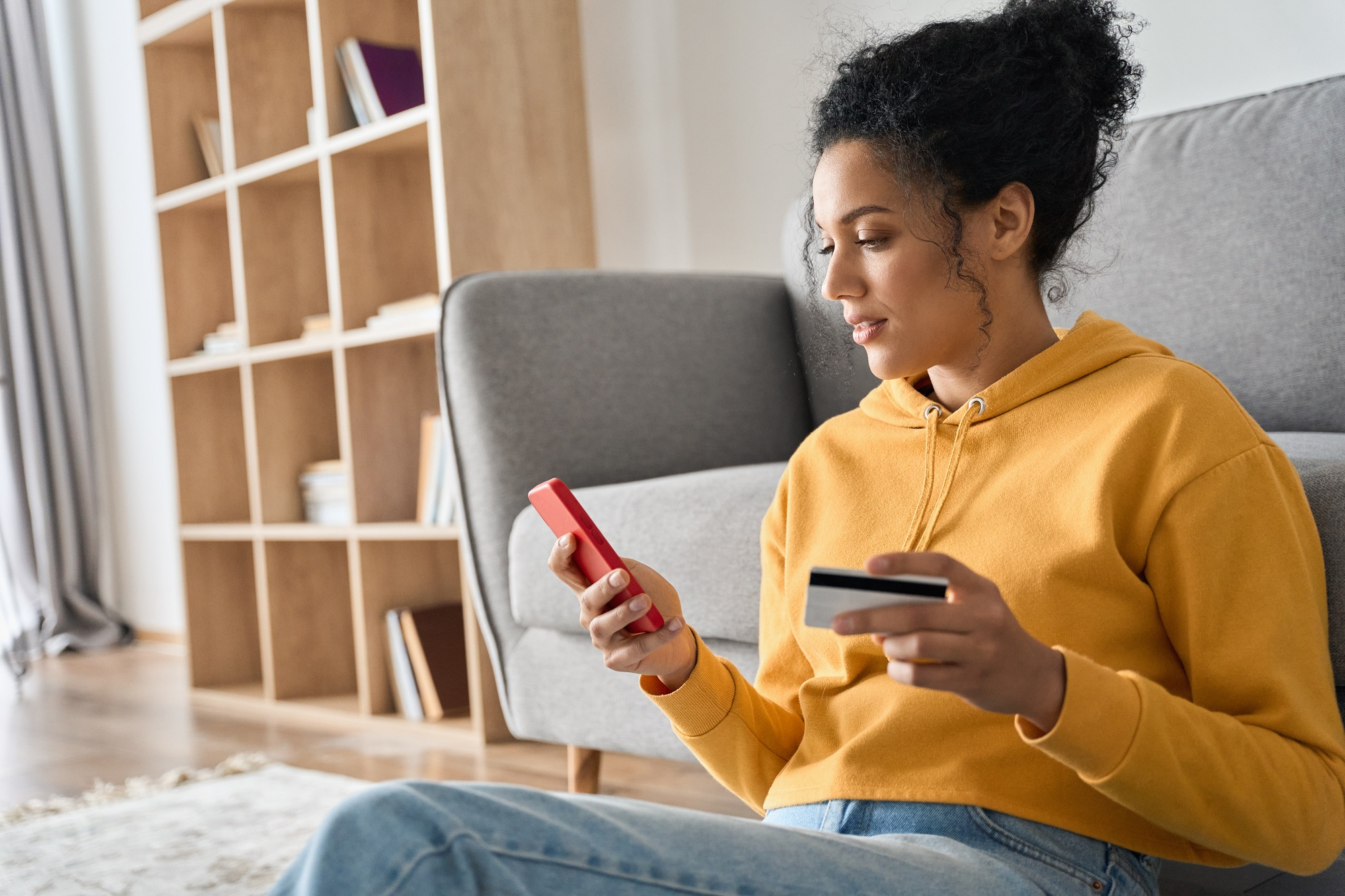 Woman sits on the floor in the living room making an online donation to charity on her phone