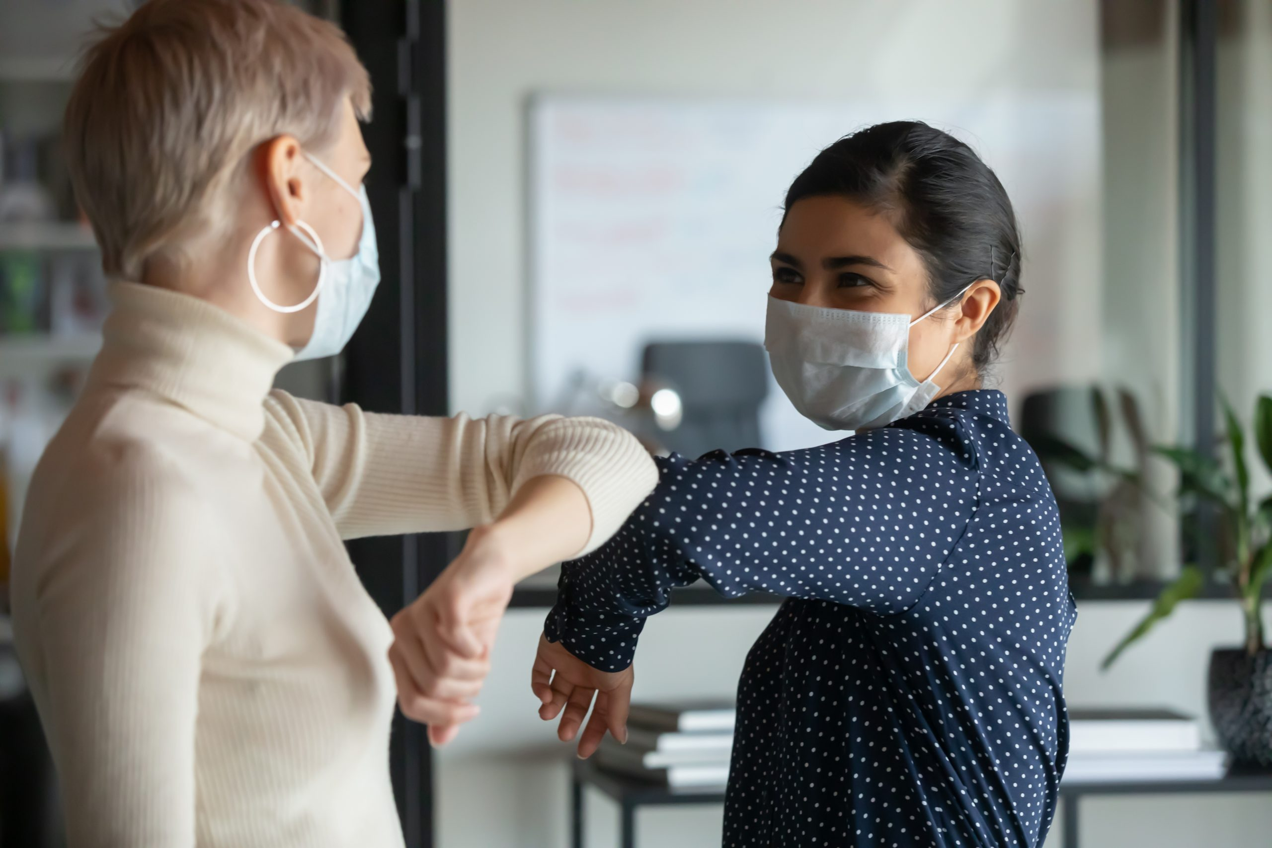 Smiling diverse female colleagues wearing protective face masks greeting bumping elbows at workplace