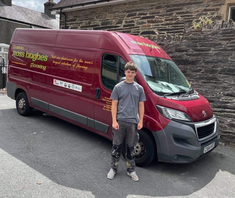 Young man stands next to van