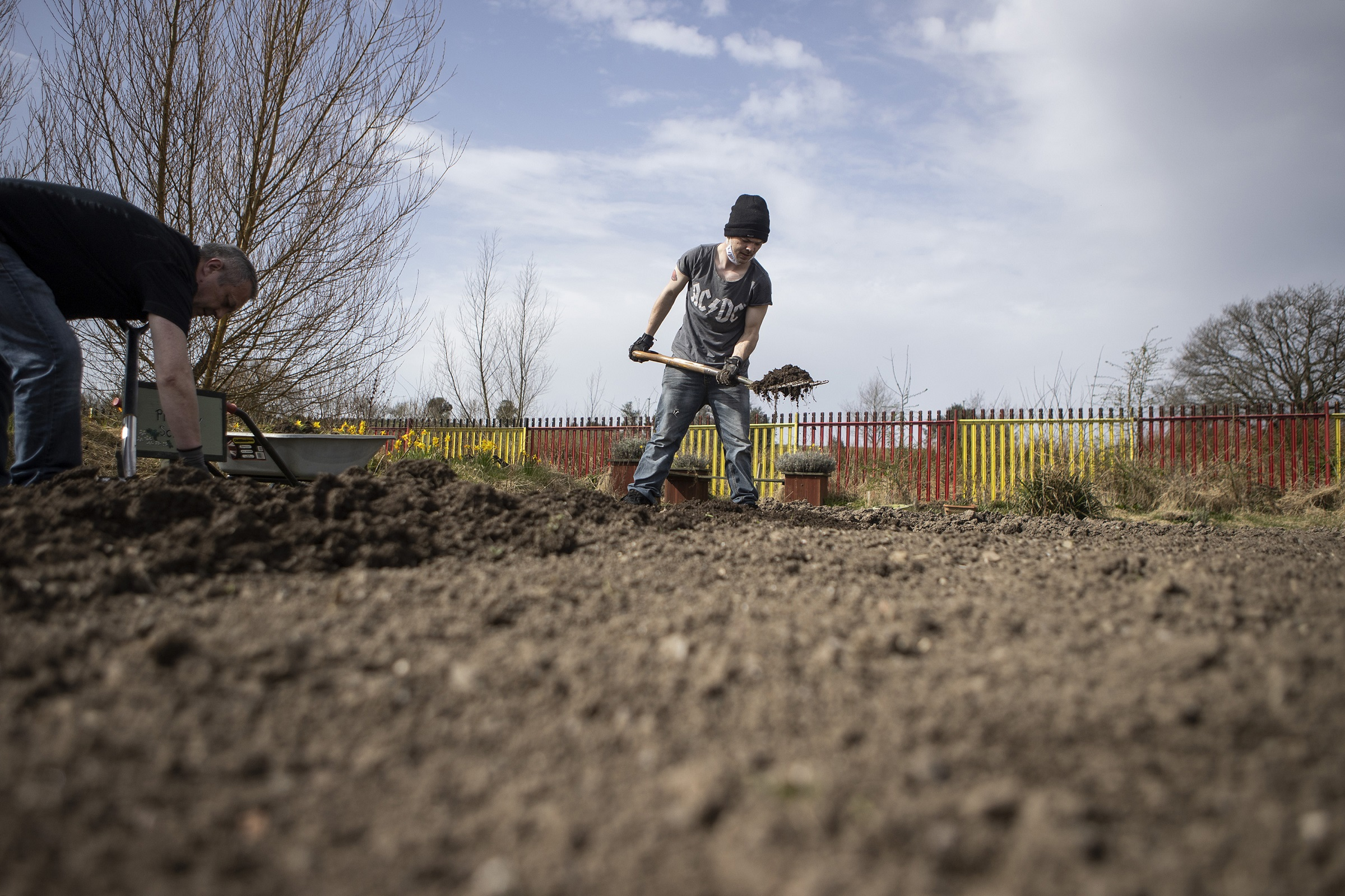 Young man shovels earth in an allotment as part of an outdoor activity run by Platfform, a mental health and social change charity in Wales