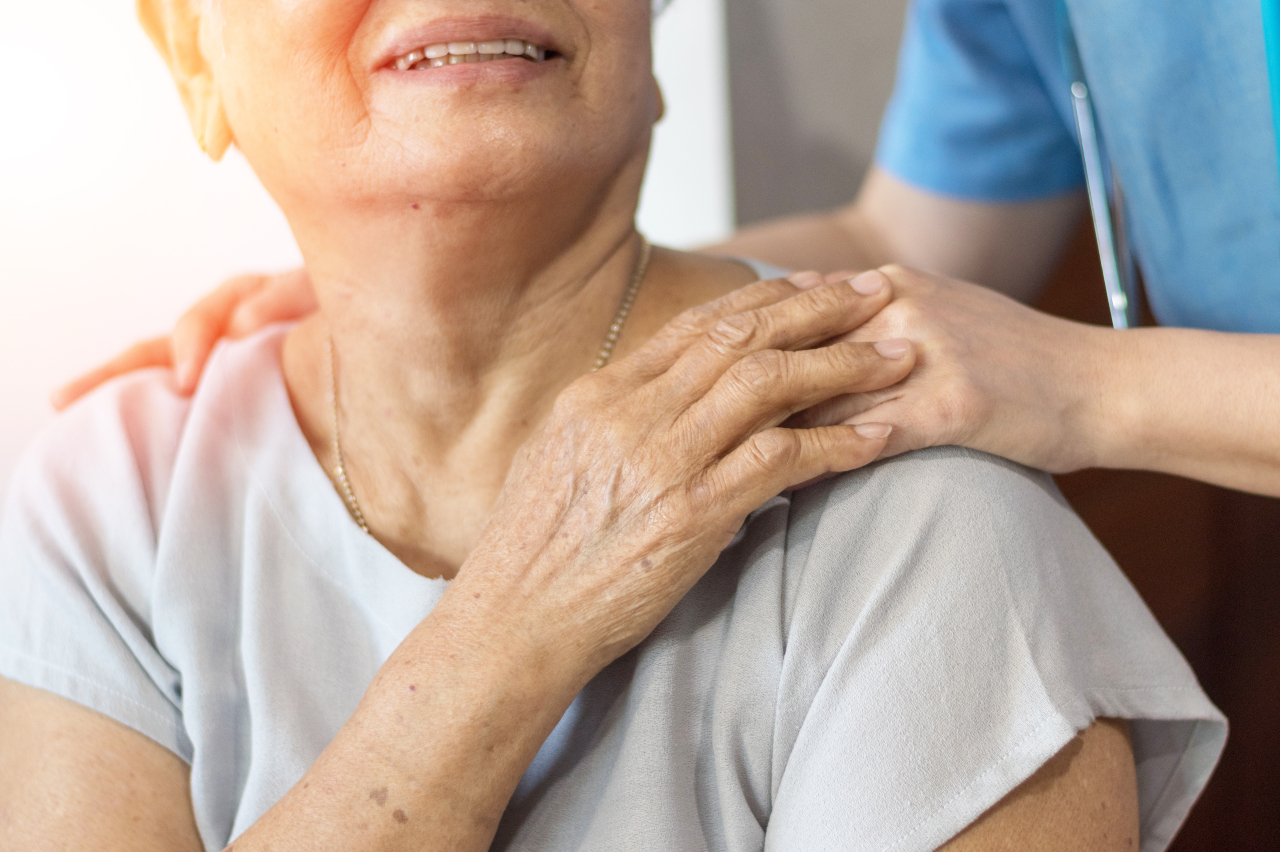 Elderly female hand holding hand of young caregiver