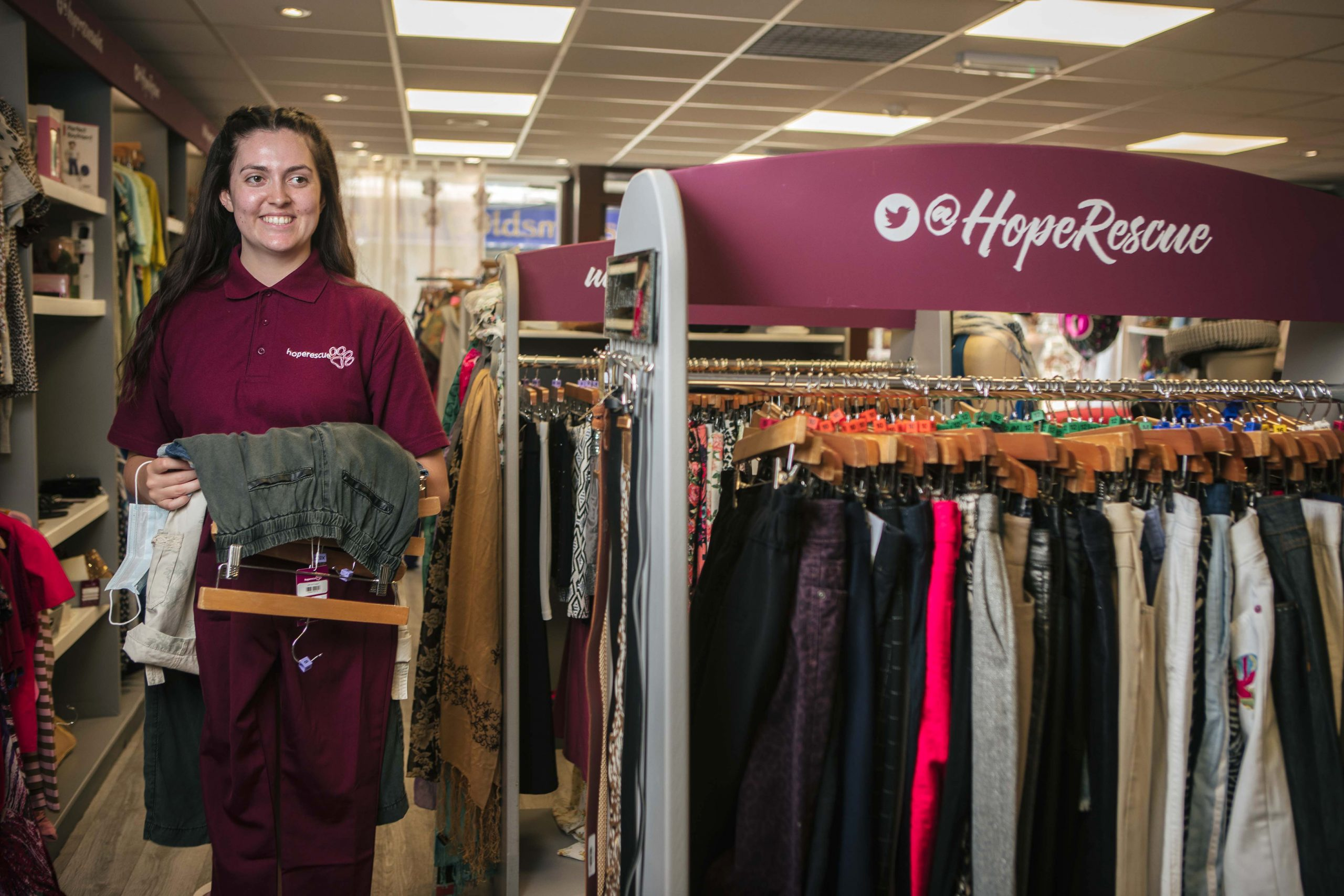 Young woman stands holding clothes in front of clothes rail in shop