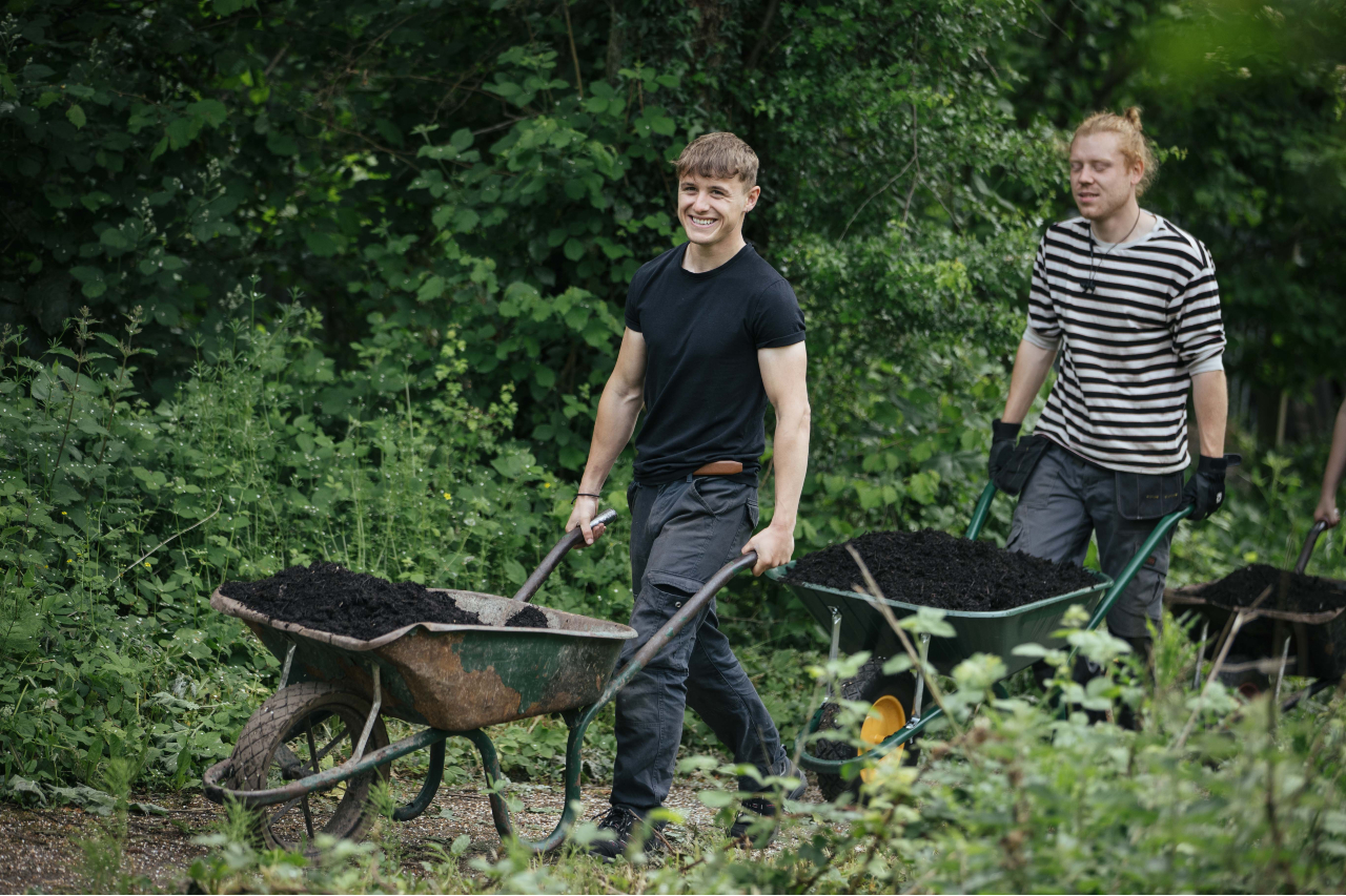 Two smiling volunteers push wheelbarrows