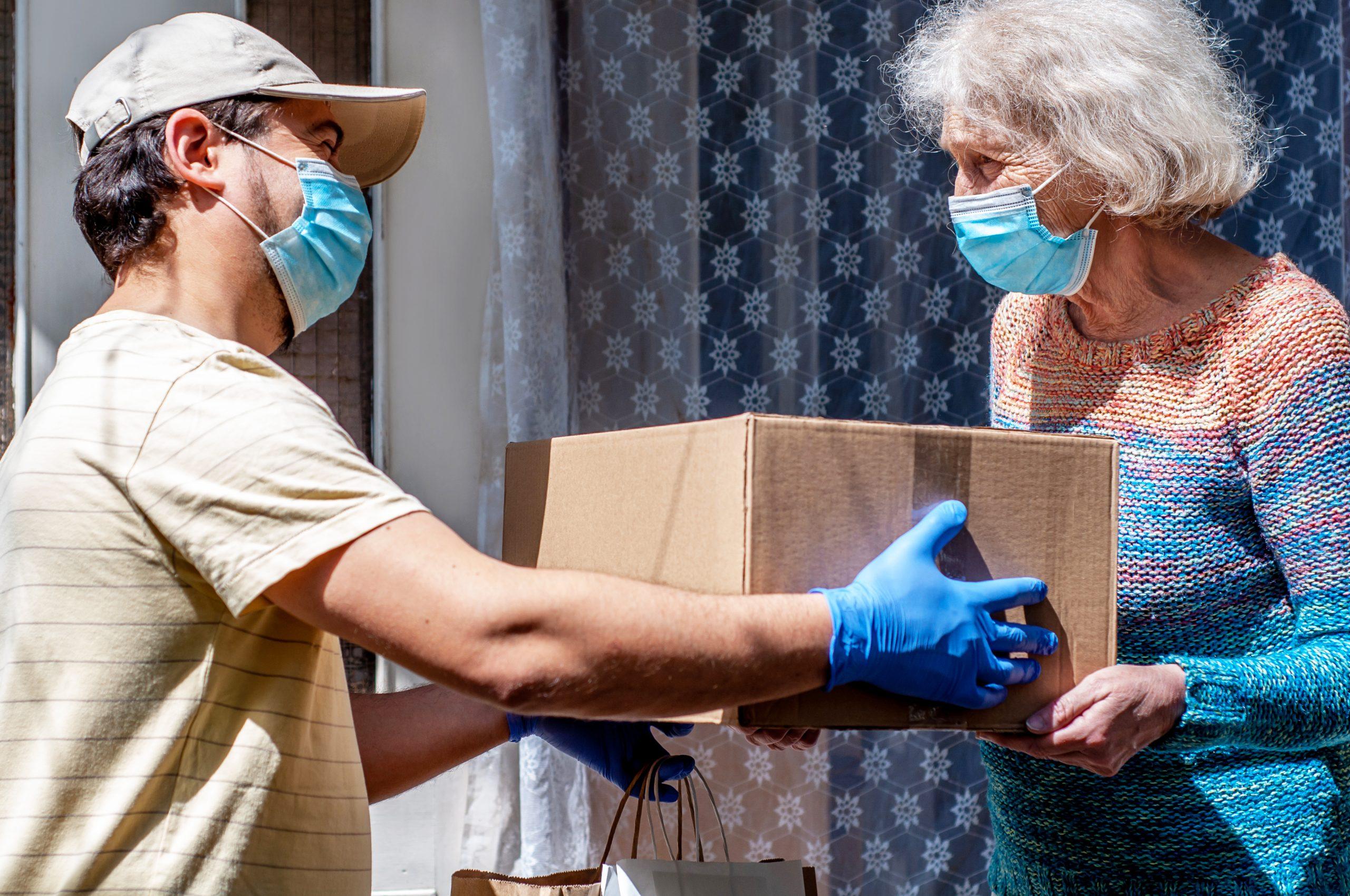 masked volunteer gives food box to elderly masked woman